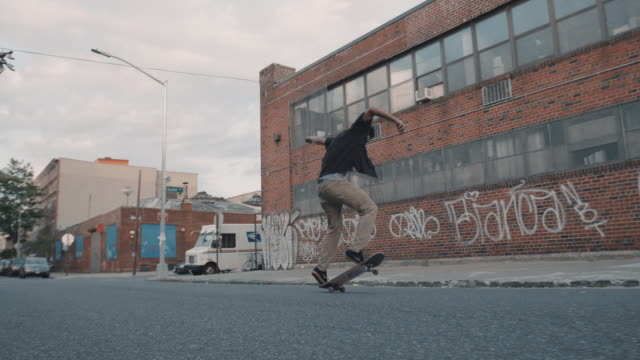 A young, mixed race millennial skateboards through the streets of Brooklyn, NYC - slow motion - wide angle