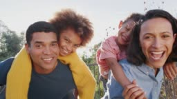 Young mixed race parents parents and their kids having fun in the garden looking to camera, close up