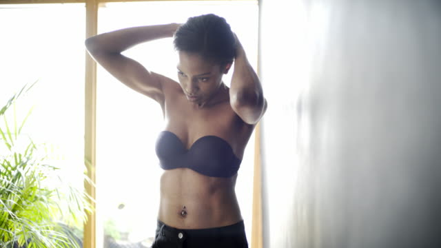 a young mixed race woman fixing up her hair - belly button piercing stock videos & royalty-free footage