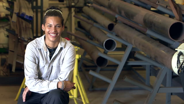 Young mixed race woman in a factory warehouse