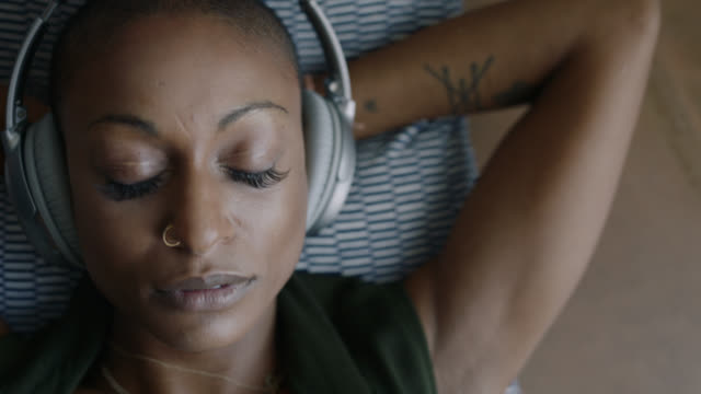 cu. young mixed race woman listening to music in headphones opens her eyes and looks at camera. - eyes closed stock videos & royalty-free footage