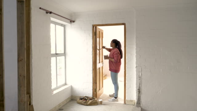 young mixed race woman painting a door with varnish - bricolage video stock e b–roll