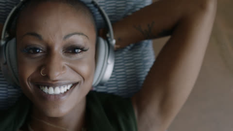 vídeos y material grabado en eventos de stock de cu. young mixed race woman rocks out while listening to music in headphones and smiles at camera. - escuchar