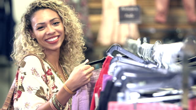 young mixed race woman shopping in clothing store - second hand stock videos & royalty-free footage