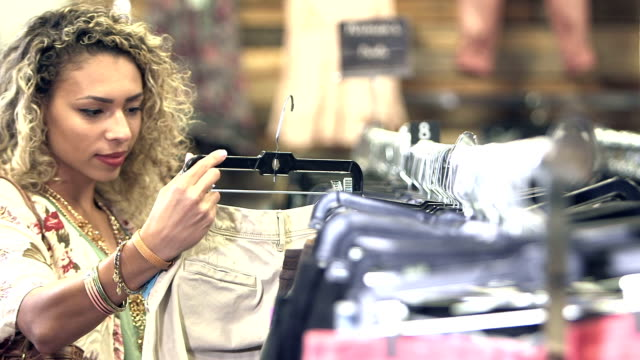 Femme de race mixte jeune shopping dans le magasin de vêtements