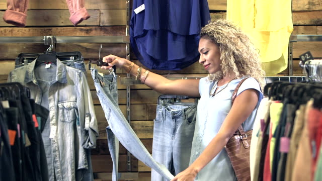 young mixed race woman shopping in clothing store - jeans stock videos & royalty-free footage