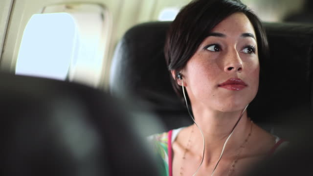 Young mixed race woman sitting on aeroplane