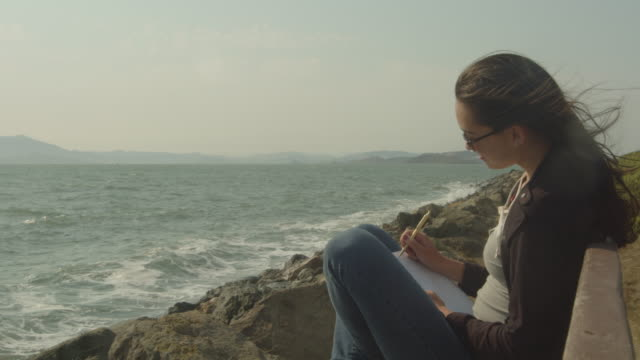 A young mixed race woman writing in her journal by the water.