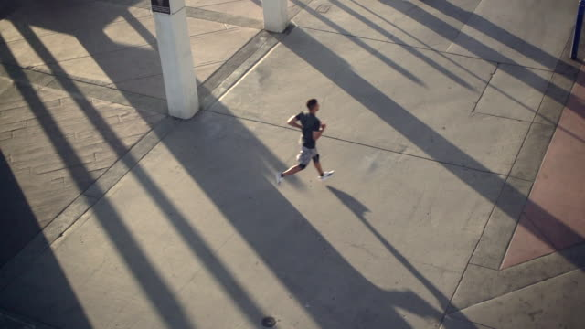 sm ws young mixed raced man running  at sunset. - city life stock videos & royalty-free footage