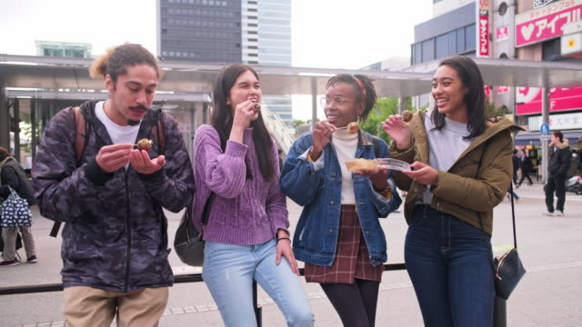 young mixed-ethnic group enjoying outdoor snack in tokyo - standing stock videos & royalty-free footage