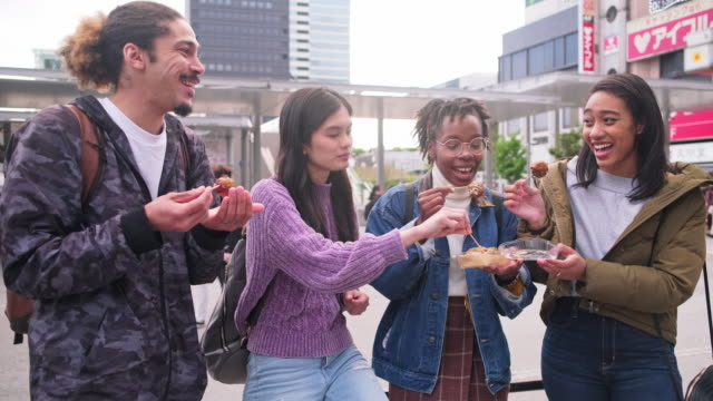 young mixed-ethnic group enjoying outdoor snack in tokyo - quattro persone video stock e b–roll