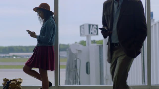 vídeos y material grabado en eventos de stock de slo mo. young mixed-race female traveler leans agaist airport terminal window as traveler passes. - sala de embarque del aeropuerto