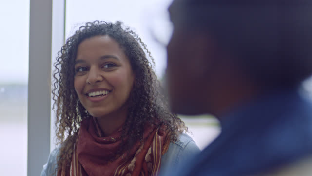 vidéos et rushes de young mixed-race female traveler smiles while listening to friends talking at airport terminal gate. - jeunes femmes