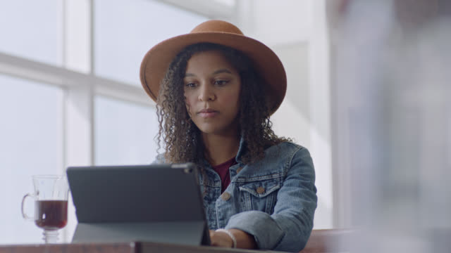 young mixed-race female traveler works on tablet at airport terminal cafe. - internet café stock-videos und b-roll-filmmaterial