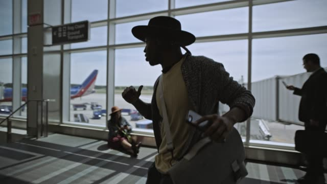 slo mo. young mixed-race male traveler dances amoung travelers in airport terminal near gate. - performance stock videos & royalty-free footage