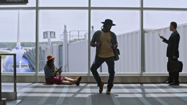 SLO MO. Young mixed-race male traveler dances in airport terminal near gate.