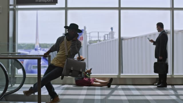 vidéos et rushes de young mixed-race male traveler dances while on phone in airport terminal near gate. - voyageur