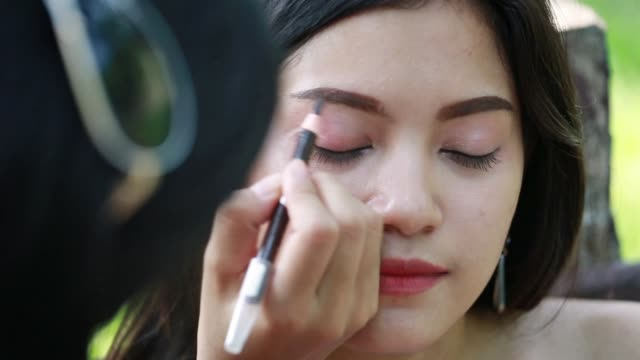 Young model doing makeup eyebrow pencil applied