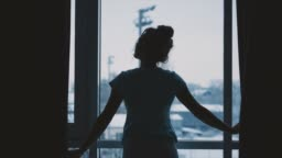 Young models in a modern high-rise house with full length windows, stretched out arms, welcoming the new day, dancing barefoot in the morning, bought a new apartment. A sense of a happy, alive, dream. Rear view