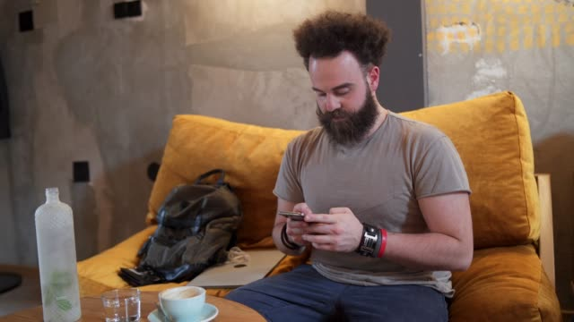 young modern man sms texting in coffee shop - modern manhood stock videos & royalty-free footage