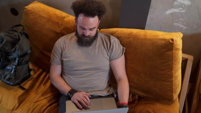 vídeos de stock e filmes b-roll de young modern man using laptop in coffee shop - masculinidade moderna