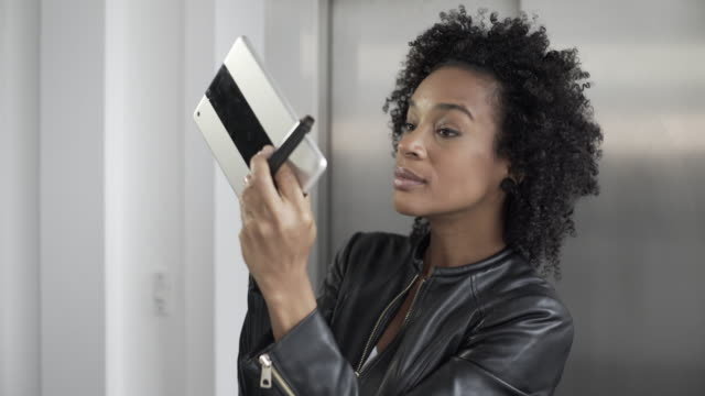 A young modern woman doing her make-up with the help of a tablet computer selfie camera.