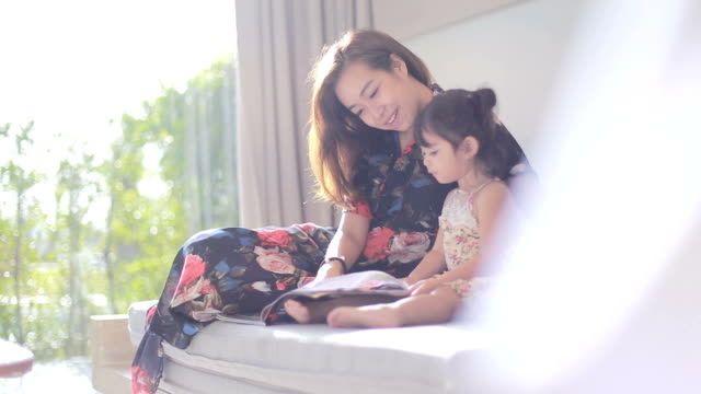 young mom reading a book to her baby girl - single parent family stock videos & royalty-free footage