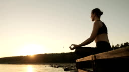 Young moman is meditating sitting on the river pier at sunset in lotus pose