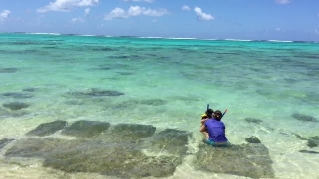 young mother age show her young daughter how to wear a snorkeling gear in a lagoon of the tropical island - cook islands stock videos & royalty-free footage