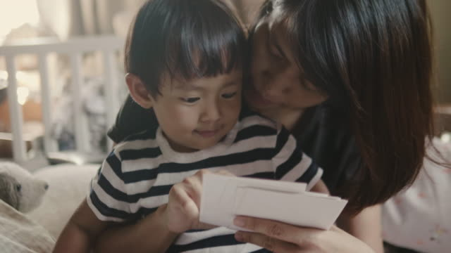 junge mutter und baby junge sitzt auf dem bett und blick auf foto. - gedächtnisstütze stock-videos und b-roll-filmmaterial