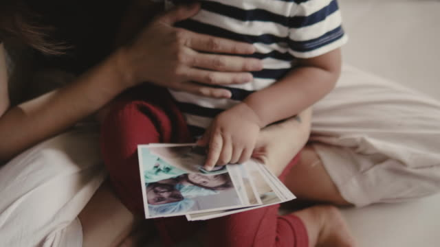young mother and baby boy sitting on the bed and looking at photo. - photo album stock videos and b-roll footage