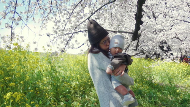 young mother and baby enjoying the spring - 0 11 mesi video stock e b–roll