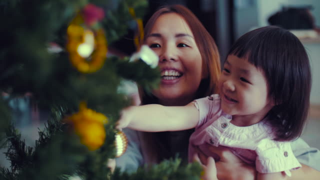 young mother and baby girl decorating christmas tree with ornaments - east asian ethnicity stock videos & royalty-free footage