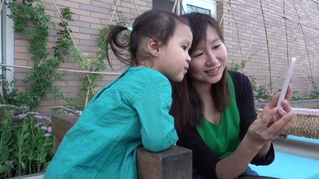 young mother and baby girl looking at smartphone - vanguardians stock videos & royalty-free footage