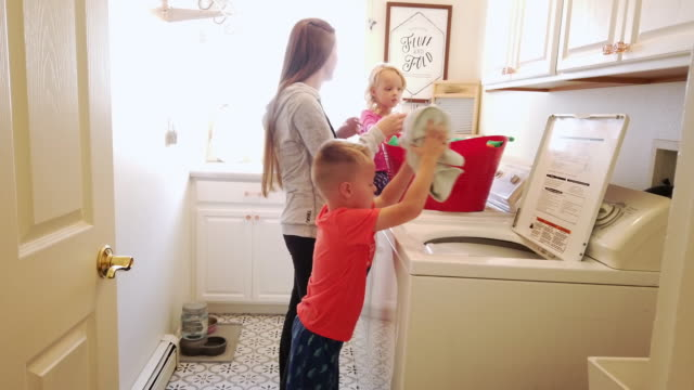young mother and children doing laundry together in a domestic home video series - tumble dryer stock videos & royalty-free footage