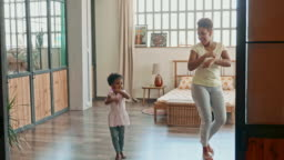 Young Mother and Daughter Doing Dance Exercises At Home