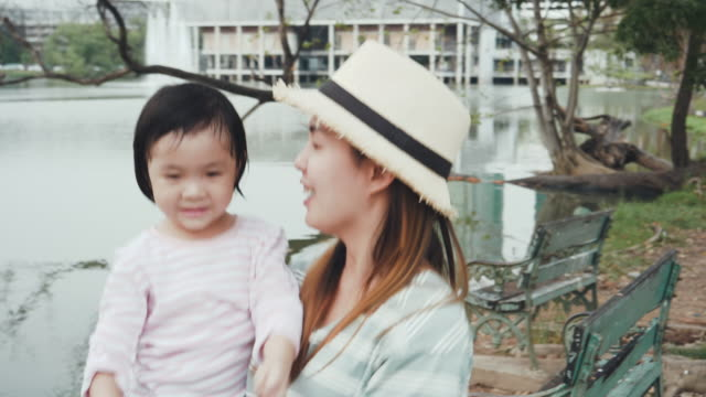 vidéos et rushes de jeune maman et la jouissance de la fille dans le parc public - famille de deux générations