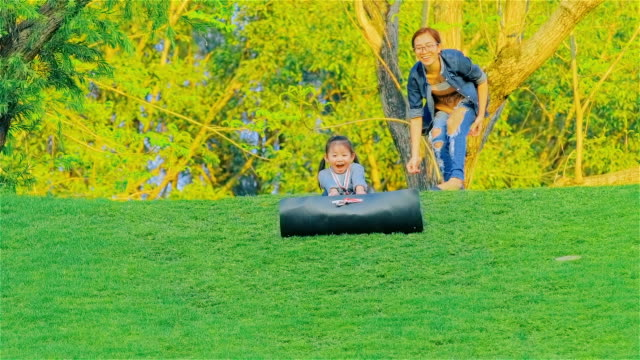 young mother and daughter having fun sliding down a grassy hill at mae moh lampang, thailand - slippery stock videos & royalty-free footage