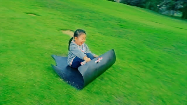young mother and daughter having fun sliding down a grassy hill at mae moh lampang, thailand - slippery stock videos and b-roll footage