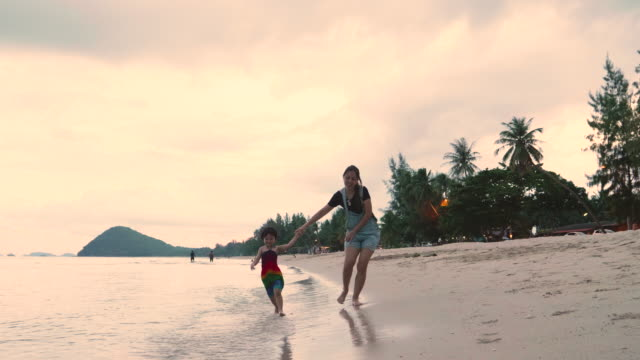 Young Mother And Daughter Holding Hands And Walking On The Beach