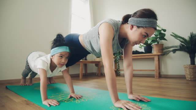 young mother and daughter making a exercises at home. - daughter stock videos & royalty-free footage