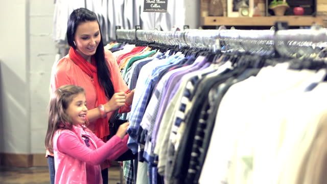 young mother and daughter shopping in clothing store - second hand stock videos & royalty-free footage