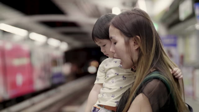 young mother and daughter waiting bts sky train in bangkok,thailand - getting on stock videos & royalty-free footage