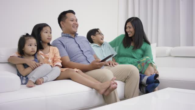 Jonge moeder en vader televisiekijken met kinderen