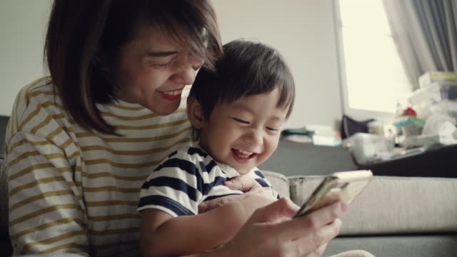 young mother and happy baby boy (12-23 months) using smart phone at home - asian stock videos & royalty-free footage