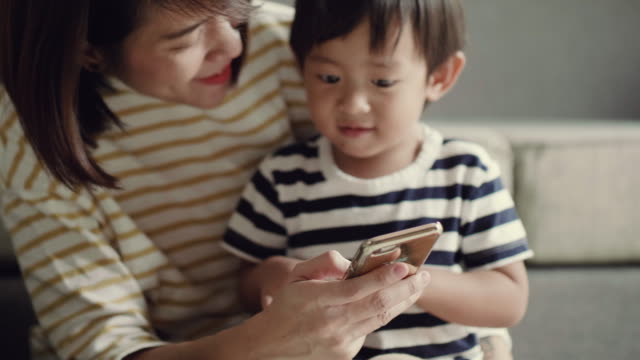 Young mother and happy baby boy (12-23 months) using smart phone at home