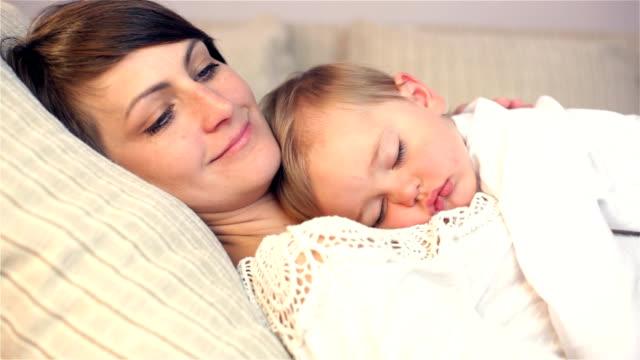 vídeos de stock, filmes e b-roll de jovem mãe e seu bebê dormindo na cama, - de braços dados
