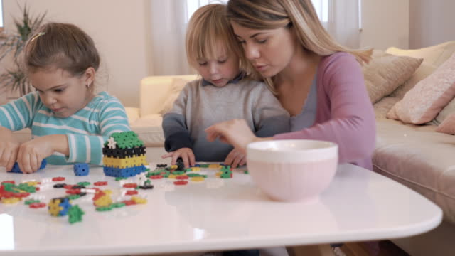 young mother and her children playing with puzzles in the living room. - puzzle stock videos & royalty-free footage
