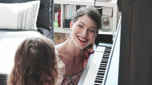 vídeos de stock e filmes b-roll de young mother and her daughter playing piano in their living room - família com um filho