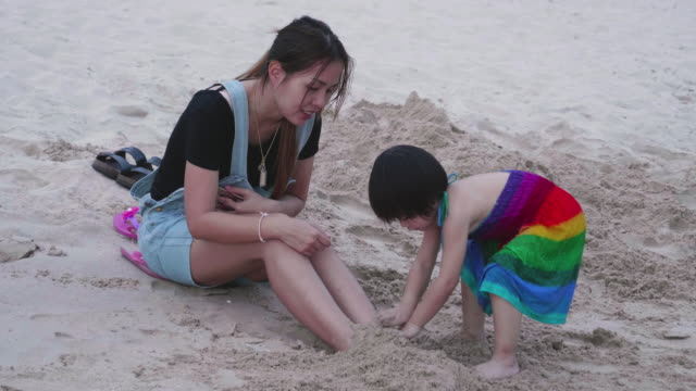 Young Mother And Her Daughter Playing With Sand On The Beach